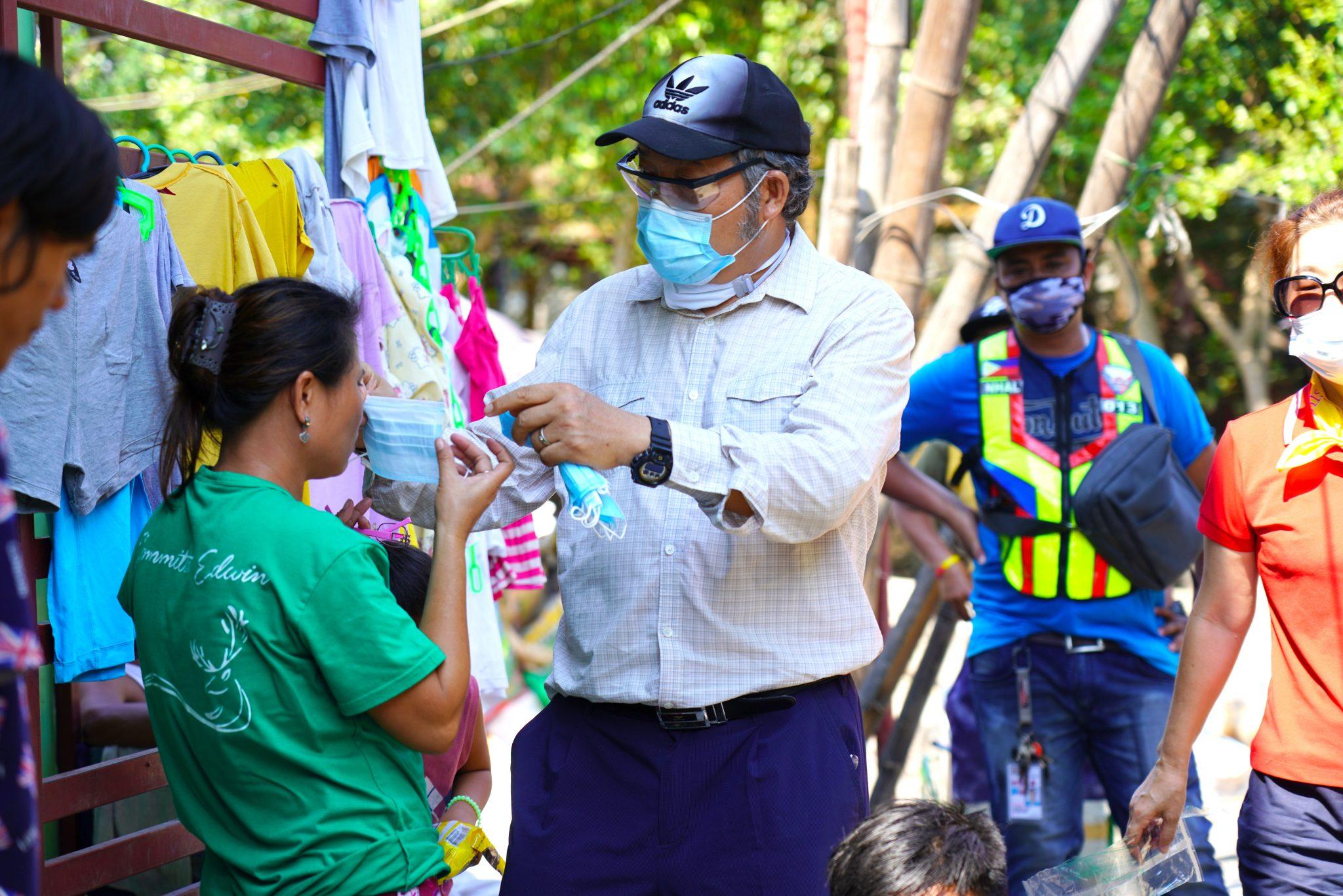 Missionary Sang Ho Kim Helping Put on Mask
